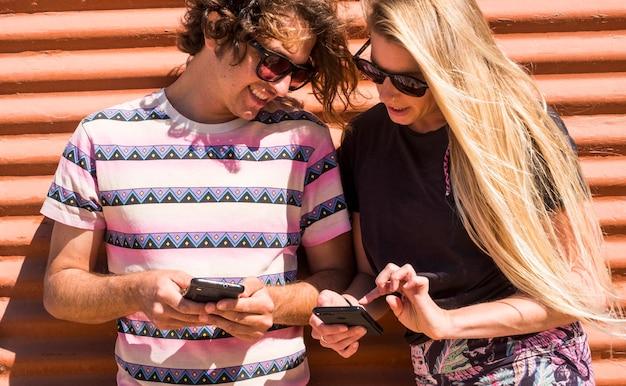 Duizendjarige jongeren koppelen elkaar met behulp van beide mobiele telefoons die naar de apparaten kijken