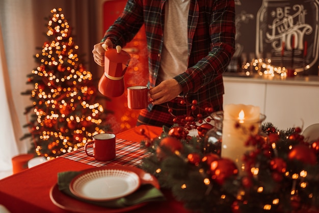 Duizendjarige koffie gieten in beker in kerstsfeer