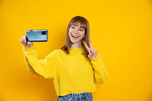 Duizendjarige neemt een selfie met behulp van slimme telefoon mobiel geïsoleerd op een gele achtergrond