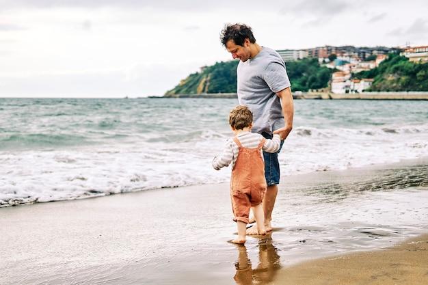 Duizendjarige vader met zijn drie jaar oude zoon spelen met de hallo aan de kust