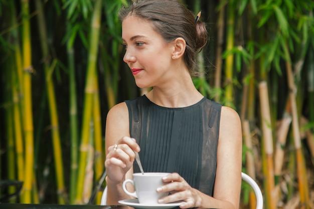 Duizendjarige vrouw die wat koffie in frankrijk drinkt
