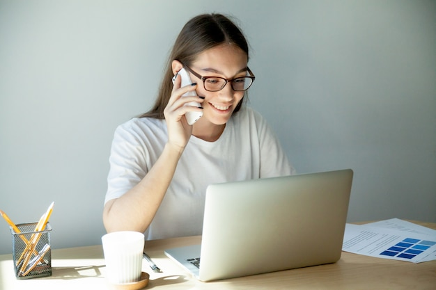Duizendjarige vrouw in glazen die op mobiel spreken en laptop met behulp van