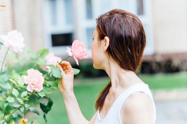 Duizendjarige vrouw van achteren die een roos ruikt in een park