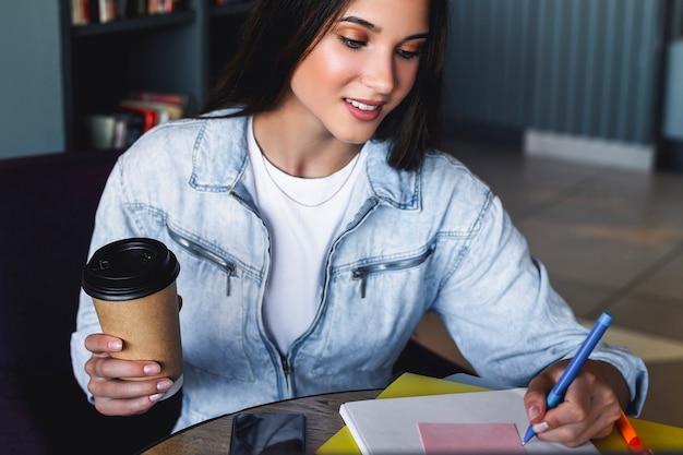 Duizendjarige vrouw zit achter een laptop en studeert op afstand. de student maakt gebruik van online mogelijkheden voor afstandsonderwijs.