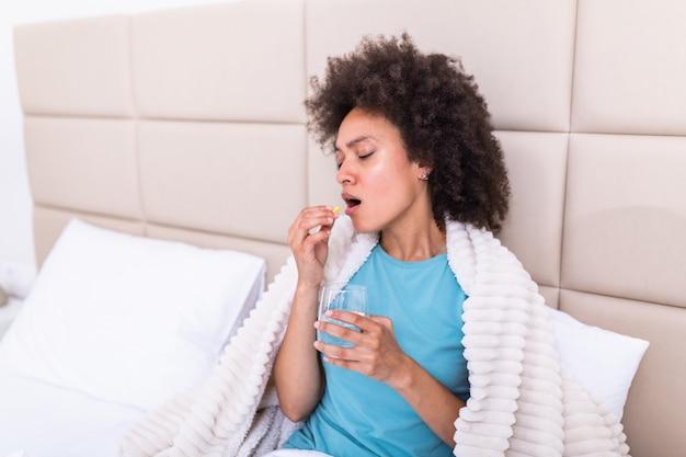 Duizendjarige zieke vrouw die pijnstillers gebruikt om maagpijn te verlichten, zit 's ochtends op bed. zieke vrouw die in bed met hoge koorts ligt.