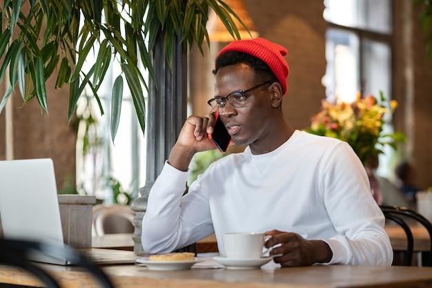 Duizendjarige zwarte man praten op mobiele telefoon