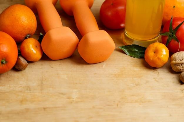 Dumbbell, sinaasappelsap, fruit en noten op de houten tafel, sport en gezondheids lifestyle concept