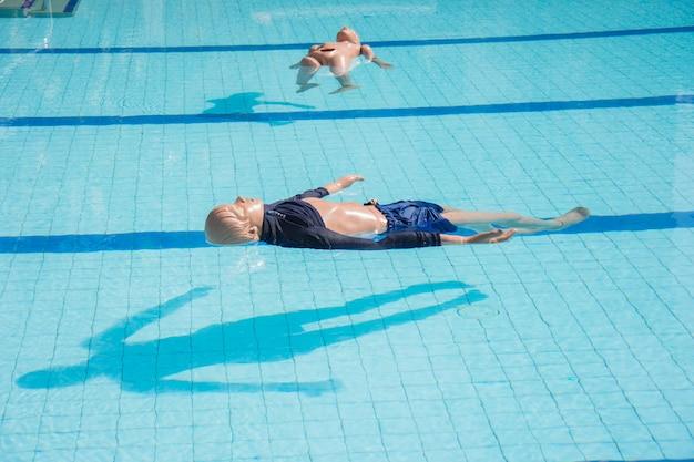 Dummy-drenktraining volwassen en kind zweven in het zwembad