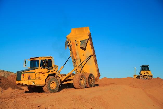 Dumpende vrachtwagen en bulldozer op de bouwplaats
