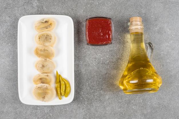 Dumplings gevuld met vlees op een witte plaat met olijfolie