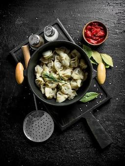 Dumplings in een pot met tomatenpuree, laurier en kruiden
