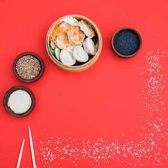 Dumplings in steamer met korianderzaad; zwart en wit sesamzaad kom op rode achtergrond