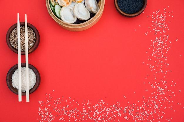 Dumplings in steamer met korianderzaad; zwart en wit sesamzaadjes op rode achtergrond