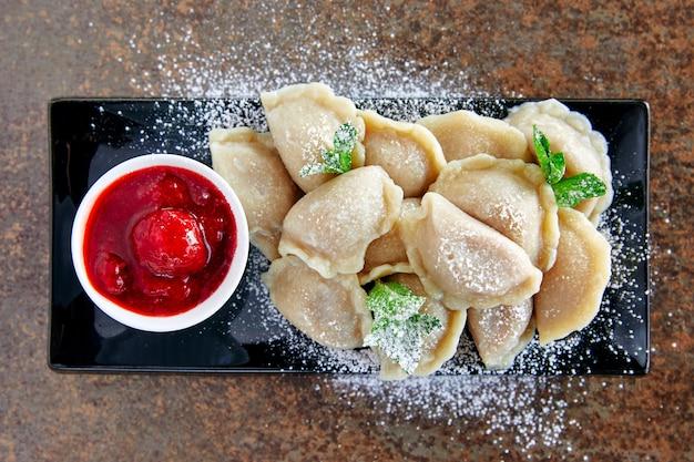 Dumplings met aardbeienjam, zure room gelegd op plaat versierd met muntblaadjes en poedersuiker