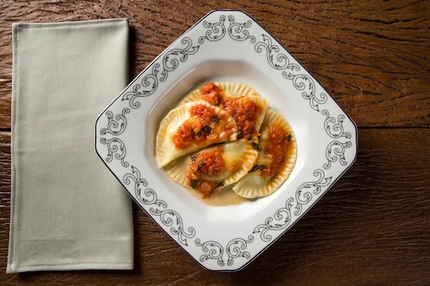 Dumplings met vlees met tomaat op een bord - pierogi