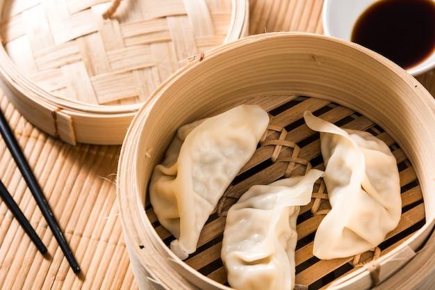 Dumplings of gyoza geserveerd in traditionele stoomboot en sojasaus op bamboemat
