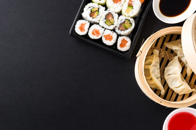 Dumplings of gyoza geserveerd in traditionele stoomboot en sushi op zwart. bovenaanzicht copyspace