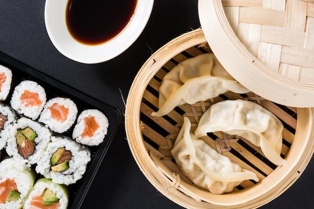Dumplings of gyoza geserveerd in traditionele stoomboot en sushi op zwart. plat liggende top-down compositie