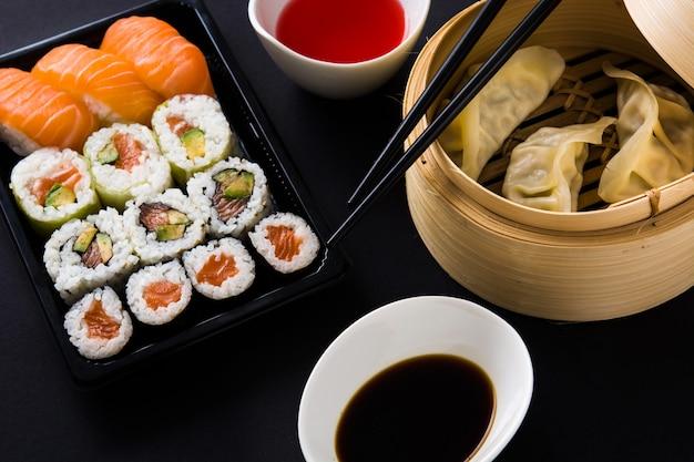 Dumplings of gyoza geserveerd in traditionele stoomboot en sushi op zwart