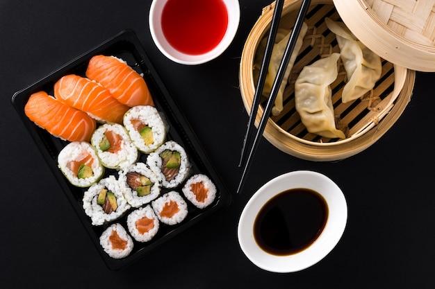 Dumplings of gyoza geserveerd in traditionele stoomboot en sushi op zwarte bovenaanzicht