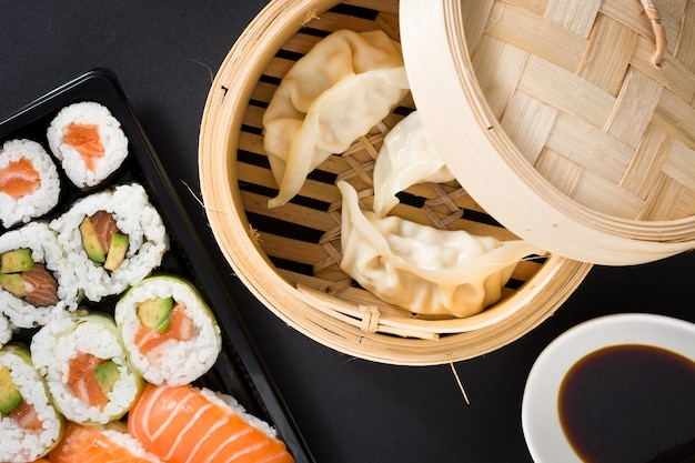 Dumplings of gyoza geserveerd in traditionele stoomboot en sushi op zwarte plat lag top-down samenstelling