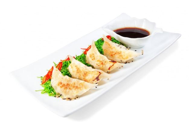 Dumplings, ravioli gevuld met zeevruchten. met zwarte azijn.