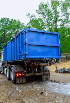 Dumpster in de buurt van een afvalloze metalen container zonder deksel staat vol met bouwafval dat in het gebouw in aanbouw staat