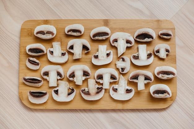 Dun gesneden verse rauwe champignons voor het bereiden van vegetarische gerechten. gezond dieet