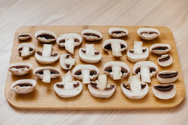 Dun gesneden verse rauwe champignons voor het bereiden van vegetarische gerechten. gezond dieet.