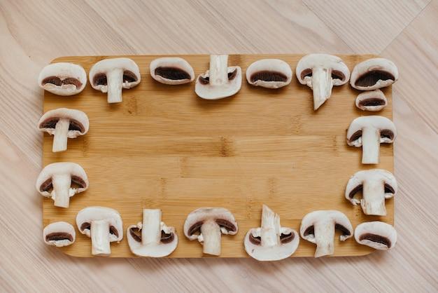 Dun gesneden verse rauwe champignons voor het bereiden van vegetarische gerechten