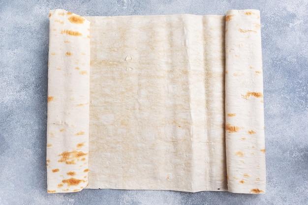 Dunne armeense lavash rolde in een rol. textuur van natuurlijk broodbaksel.