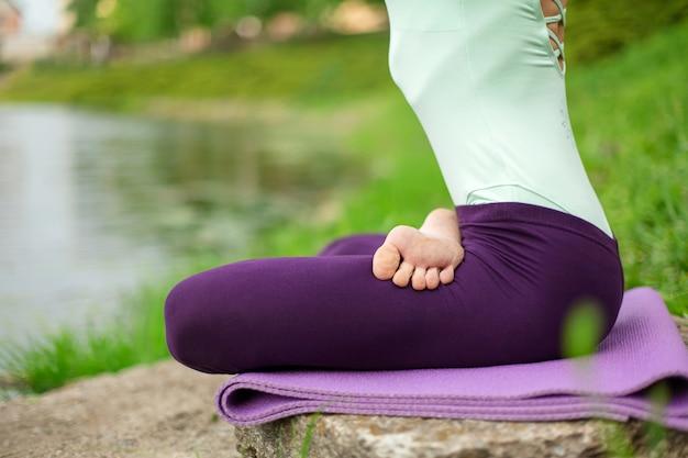 Dunne brunette meid speelt sport en voert mooie en verfijnde yogahoudingen uit in een zomerpark, weelderig groen bos en de rivier op de scène, vrouw doet oefeningen op een yogamat