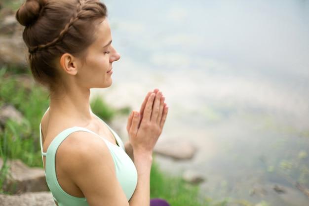 Dunne brunette vrouw speelt sport en voert mooie en verfijnde yogahoudingen uit in een zomerpark.