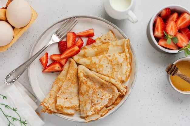 Dunne crêpes pannenkoeken met roomkaas, verse aardbeien en ingrediënten voor het maken van ontbijt. bovenaanzicht.