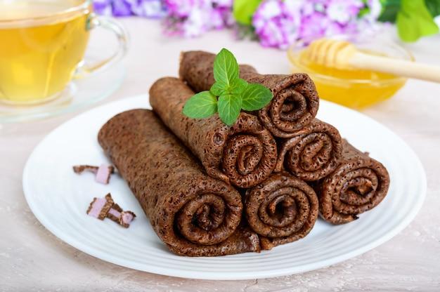 Dunne, delicate chocoladepannekoeken, gerold, op een stapel op een witte plaat gelegd en een kopje kruidenthee met honing