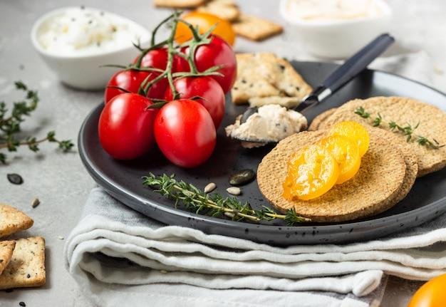 Dunne krokante volkoren crackers met roomkaas en tomaten op een zwarte plaat.