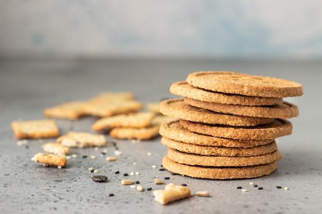 Dunne krokante volkoren crackers met zaden op grijs beton.