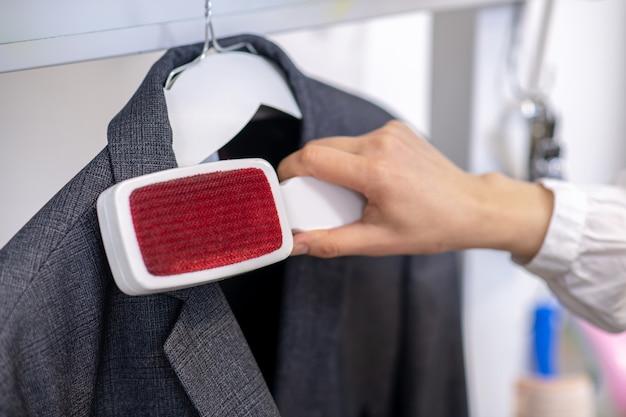 Dunne nette vrouwenhand reinigt jas gemakkelijk nauwkeurig met borstel, gezicht is niet zichtbaar