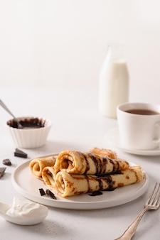 Dunne pannenkoeken met chocolade en zure room als broodjes op wit