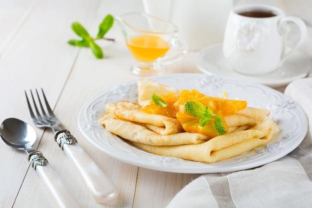 Dunne pannenkoeken met sinaasappel-citrussaus voor ontbijt op een lichte ondergrond
