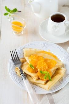 Dunne pannenkoeken met sinaasappel-citrussaus voor ontbijt op lichte achtergrond. selectieve aandacht.