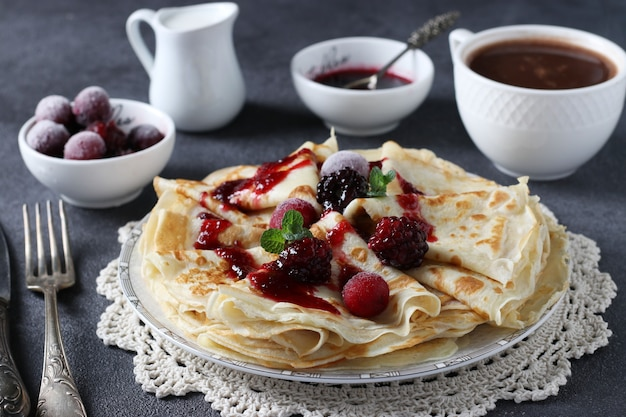 Dunne pannenkoeken met tarwebloem, eieren en kefir, geserveerd met bessen, jam en kopje koffie op donkergrijze tafel. detailopname