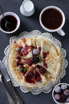 Dunne pannenkoeken met tarwebloem, eieren en kefir, geserveerd met bessen, jam en kopje koffie op grijze tafel. uitzicht van boven