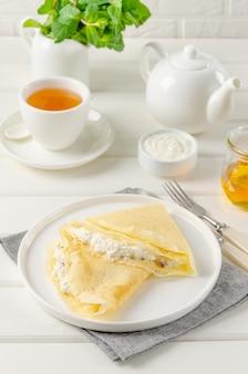 Dunne pannenkoeken of pannenkoeken met kwark, rozijnen, honing en zure room