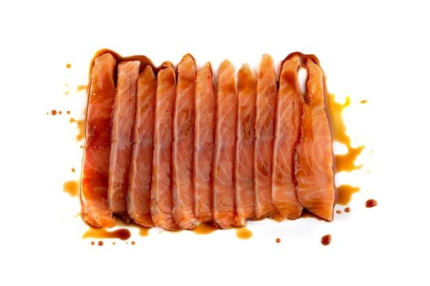 Dunne plakjes rauwe bevroren zalmfilet met sojasaus geïsoleerd. stukjes verse rode vis of forel sashimi close-up