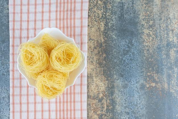 Dunne spaghettis in de kom op handdoek, op het marmeren oppervlak.