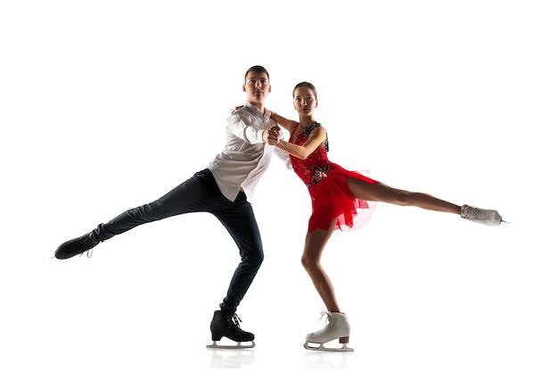 Duo kunstschaatsen geïsoleerd op een witte muur met copyspace. twee sporters oefenen en trainen in actie en beweging.