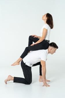 Duo van acrobaten die trucs tonen die op wit worden geïsoleerd