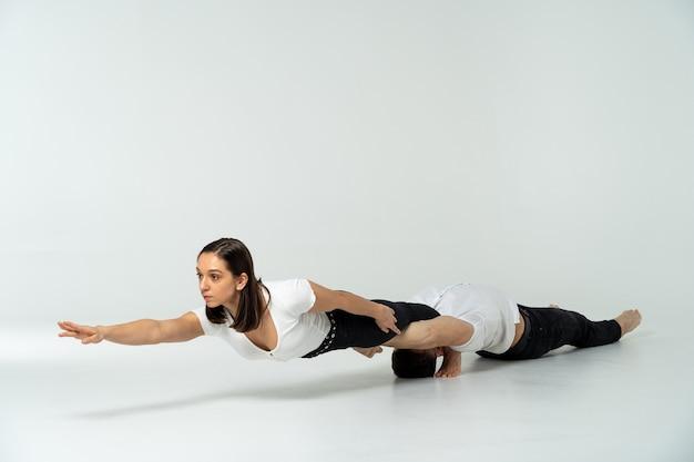 Duo van acrobaten met trucs, die op wit worden geïsoleerd.