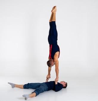 Duo van mannelijke acrobaten tonen truc van hand tot hand, geïsoleerd op wit